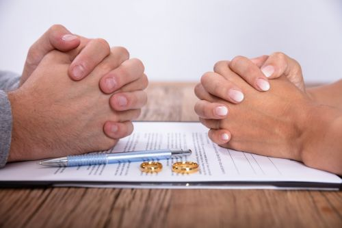 Couple's Hands With Divorce Agreement And Golden Wedding Rings